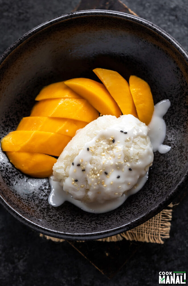 sticky rice topped with coconut sauce and served with sliced mangoes on the side in a black bowl