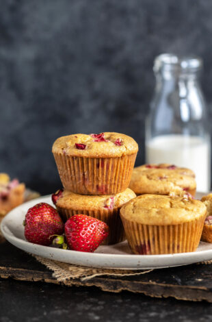 2 strawberry muffins stacked together with 2 more placed on the side and fresh strawberries placed in the front of the plate