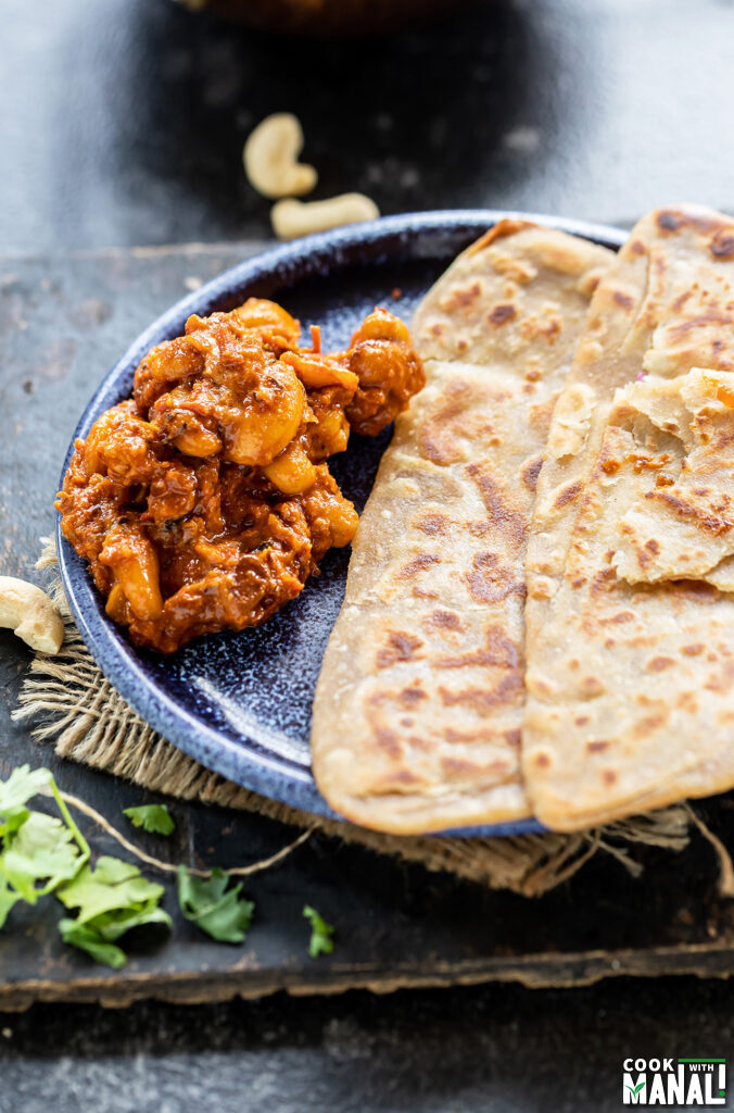 cashew curry served with parathas on a plate