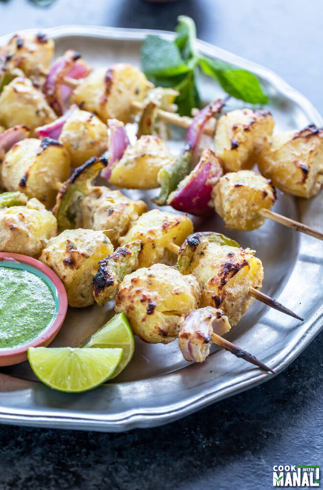 grilled baby potatoes, onions and peppers arranged on skewers with a bowl of chutney and lime wedge on the side