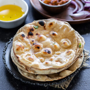stack on rotis with bowl of ghee and bowl of curry in the background