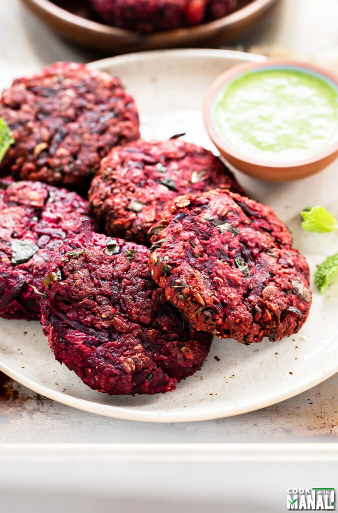 beetroot tikkis arranged on a plate with bowl of chutney on the side