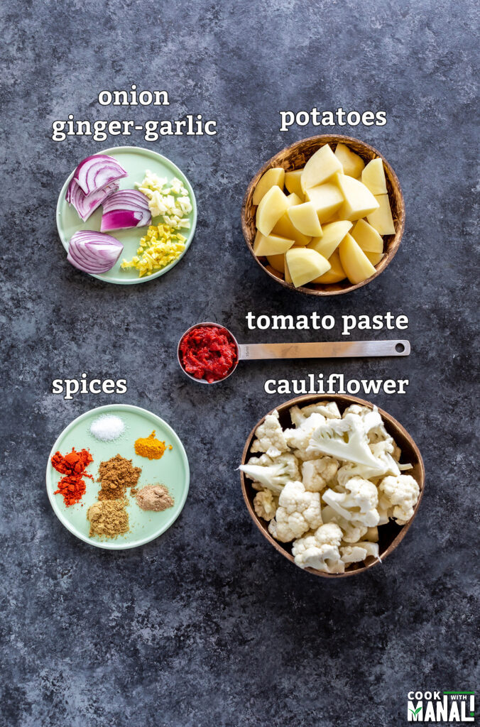 ingredients for aloo gobi arranged on a board