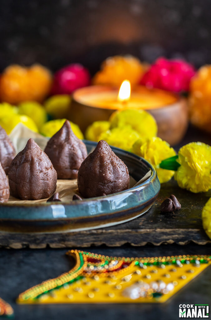 chocolate modaks placed on a plate with garlands placed on sides and candles in the background