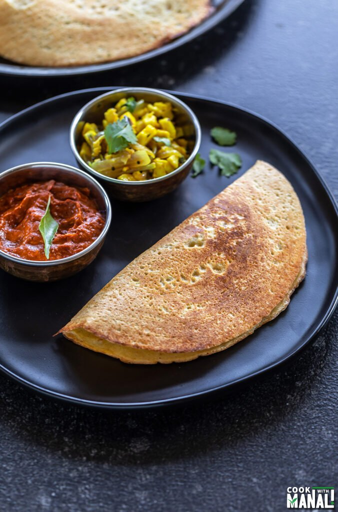 a dosa served on a plate with a bowl of chutney and a bowl of paneer