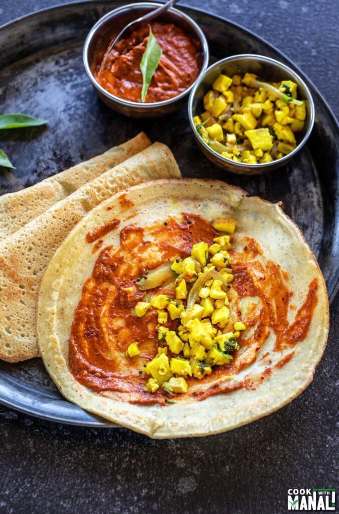 a dosa open to show the interior filled with paneer filling with bowls of chutney and paneer placed on the side