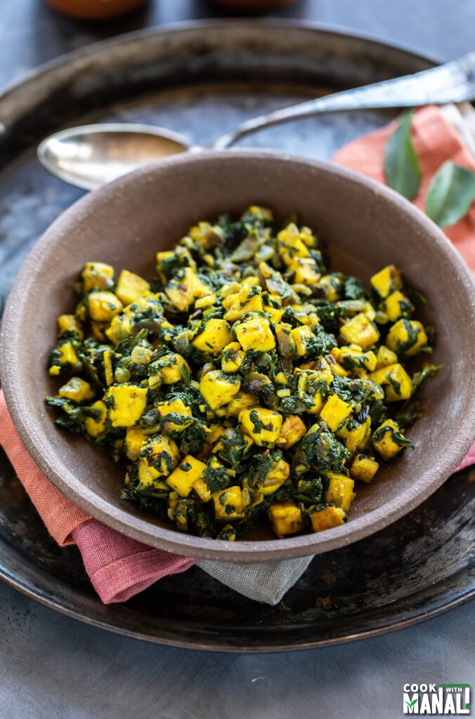 paneer and spinach stir fry served in a brown color bowl