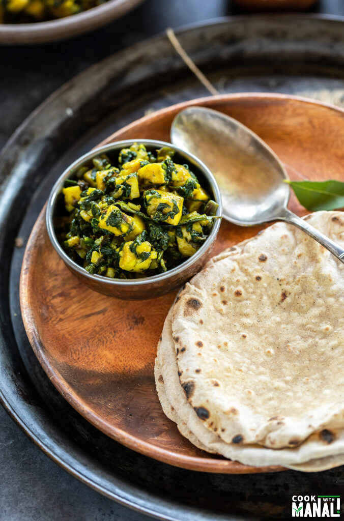 spinach paneer served in a copper bowl placed in a plate along with 2 chapatis