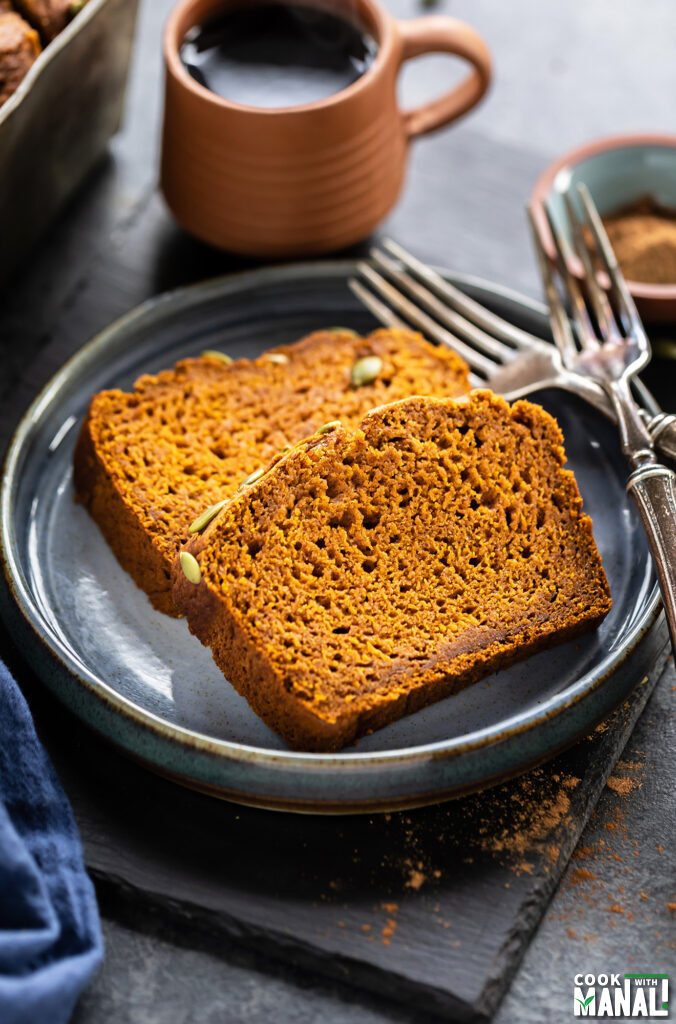 2 slices of pumpkin bread on a plate with cup of coffee in the back