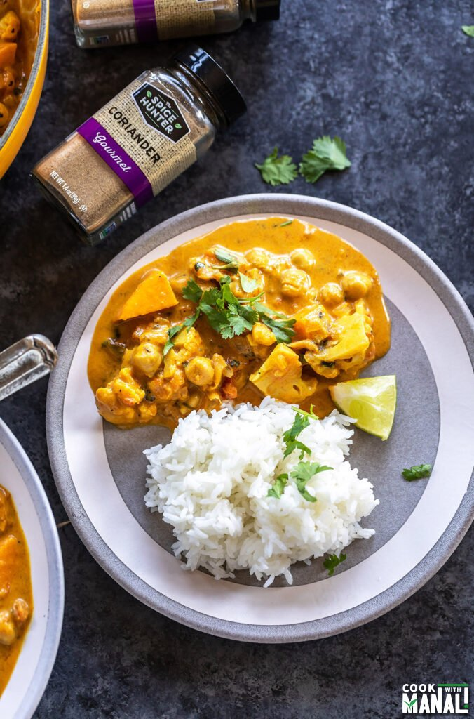 curry served with basmati rice on a plate with bottle of spices placed in the background