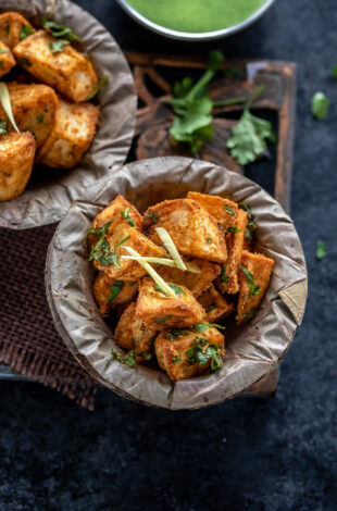 crispy fried potatoes served in a bowl and garnished with ginger juliennes and cilantro