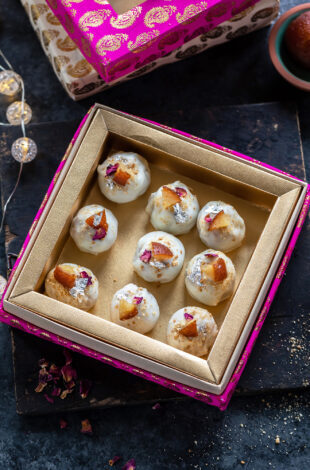 9 pieces of truffles coated with white chocolate placed in a pink color mithai box