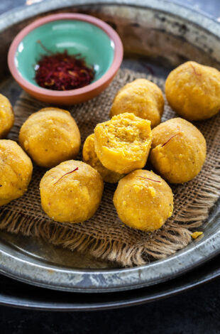 kesar badam ladoo placed on a plate with bowl of saffron strands on the side