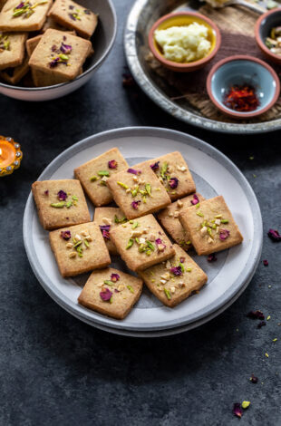 cookies topped with rose petals and pistachios placed on a plate with small bowls containing saffron placed in the background