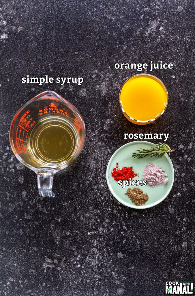 ingredients for orange rosemary mocktail arranged on a board