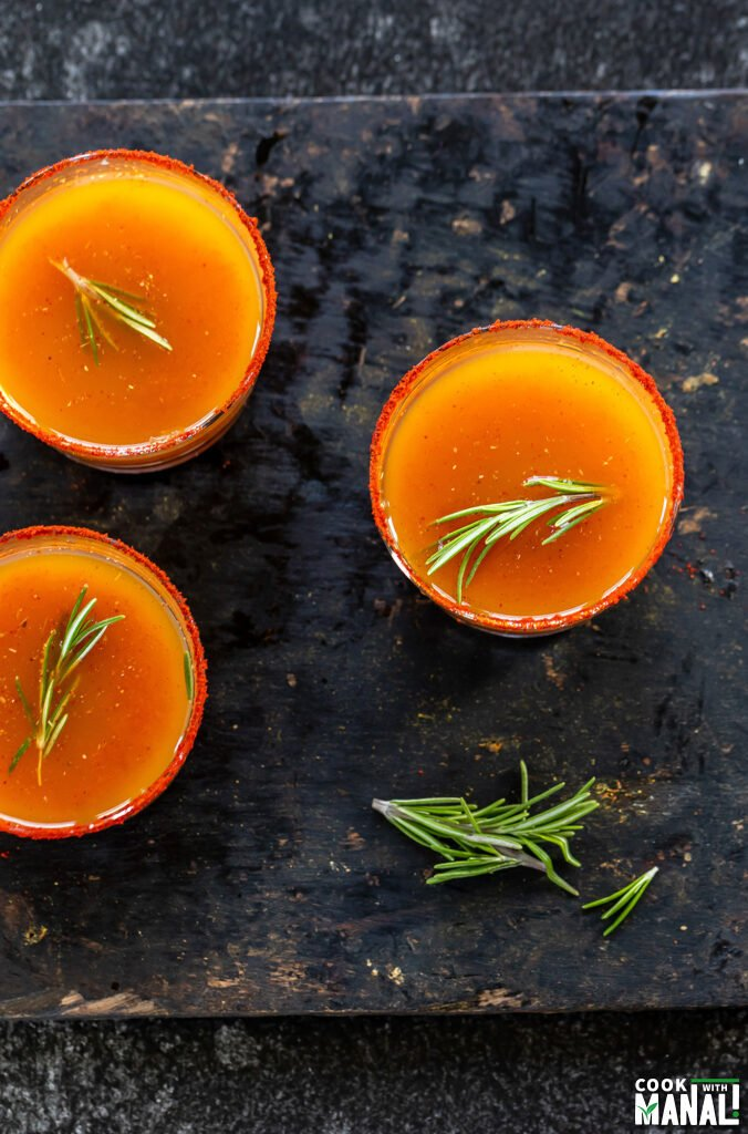 3 small glasses with orange color drink and garnished with rosemary