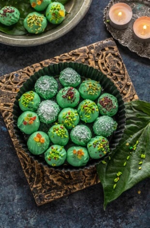 green color balls coated with candied fennel placed in a round plate with paan leaves and some tealights placed on the sides